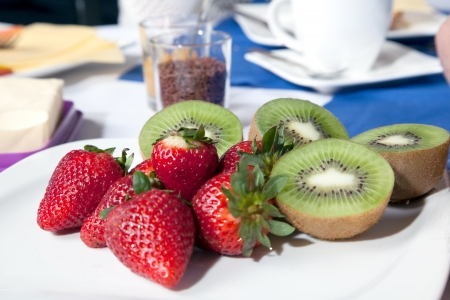 actinidia deliciosa: Closeup of a serving of whole fresh ripe red strawberries and sliced kiwifruit on a plain white plate on a breakfast table