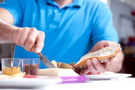 Low angle cropped view of the hands of a man buttering a slice of wholewheat bread at a breakfast table with pots of jam and marmalade alongside