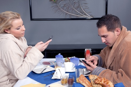 dressing gowns: Young couple seated at a table enjoying a leisurely breakfast in their dressing gowns and each looking at their mobile phones for messages