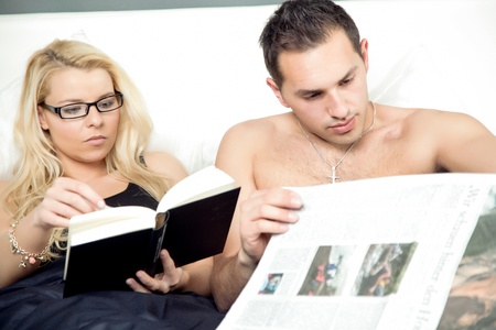 engrossed: Attractive couple reading in bed together with the woman engrossed in her book while the man concentrates on his newspaper
