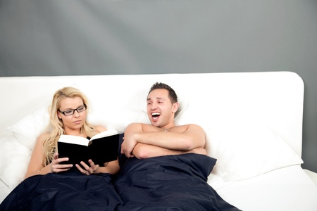 hilarity: Young man laughing heartily at his wifes book as they lie side by side together in a large bed Stock Photo