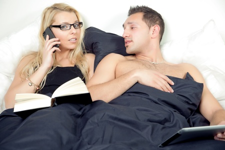 Woman taking a call on her mobile phone lying in bed watched by her inquisitive husband lying alongside her photo