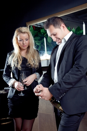 assignation: Stylish couple in black evening attire opening a bottle of champagne together to share a celebratory drink