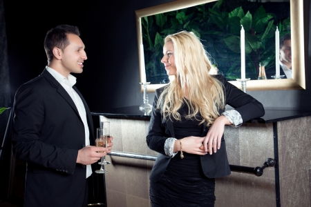 assignation: Romantic beautiful young couple in love staring into each others eyes as they stand in front of a fireplace with flutes of champagne on an elegant evening out Stock Photo