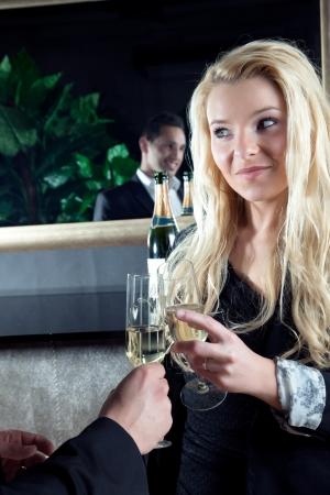 assignation: Beautiful young blond woman toasting her partner, a handsome man who is reflected in the mirror, with flutes of golden champagne as they celebrate a special moment