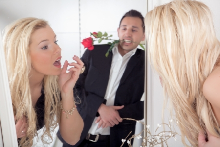 Reflection in the mirror of a nonchalant romantic man with a red rose between his teeth watching a beautiful blond woman titivating in the mirror looking up with a surprised look Stock Photo