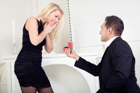 bended: Handsome young man down on bended knee proposing marriage to a beautiful blond woman who is completely overwhelmed with surprise and joy Stock Photo