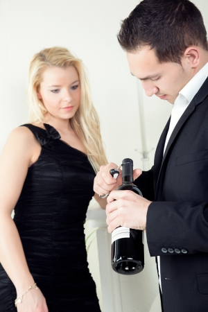 assignation: Stylish young man opening a bottle of red wine with a bottle opener watched by an elegant blond woman in a black evening dress