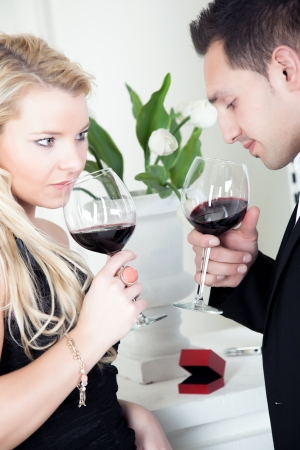 Tender young couple celebrating together holding glasses of red wine photo