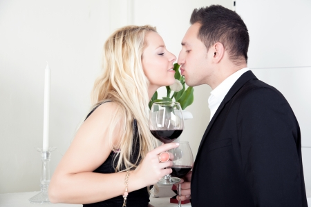 Attractive elegant young couple in love kissing while holding large glasses of red wine in their hands photo