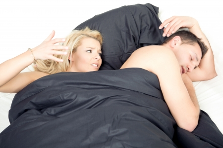 Angry frustrated woman in bed raising her fist as though to strike her sleeping husband following an argument or in an effort to quieten his snores photo