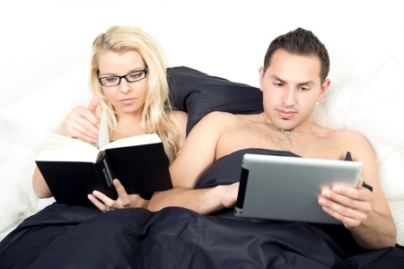 immersed: Married couple reading propped up against the pillows before sleeping with the wife reading a heavy novel while her husband enjoys an e-book on his tablet Stock Photo