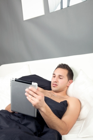 recuperating: Handsome young man lying in bed working on his tablet computer as he enjoys a relaxing day or because he is recuperating from a recent illness