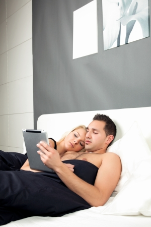 Young couple relaxing in bed lying close together while the man reads information on his tablet computer, interior of a bedroom photo