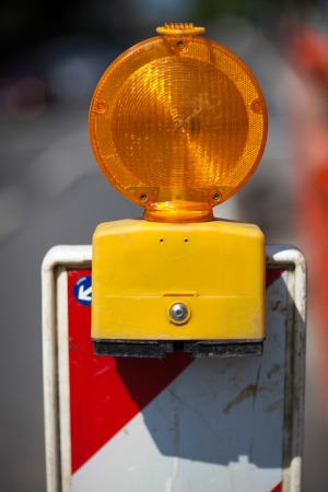 symbolization: Closeup of a temporary amber warning light set up at the side of a road warning motorists of roadworks and maintenance