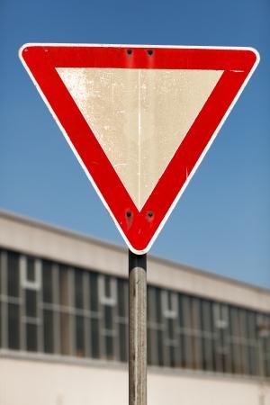 symbolization: Triangular yield traffic sign outside an urban building