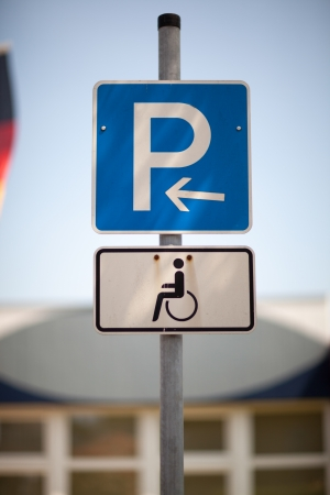 symbolization: Parking for the disabled sign on a pole in an urban environment showing a parking place reserved for handicapped people only Stock Photo