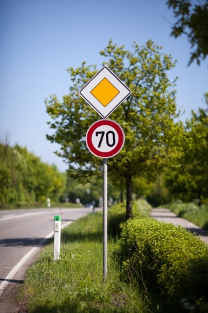 symbolization: 70 kilometres per hour speed sign and priority or right of way yellow diamond on a pole at the side of a rural road or route