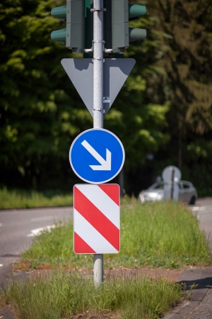 symbolization: Red and white warning chevron with a right pointing arrow warning motorists of a central island in the road and to keep to the right hand side