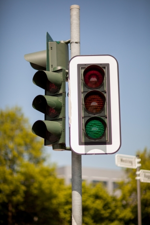 symbolization: Traffic light mounted on a pole in a town against blue sky with green light illuminated allowing cars to proceed
