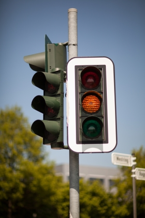 symbolization: Amber traffic light warning of a progression to a red light bringing trafic to a halt at an intersection Stock Photo
