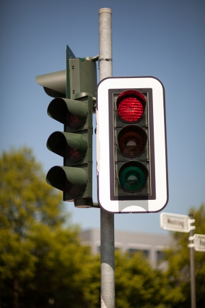 symbolization: Set of urban robots mounted on a pole with the red traffic light illuminated bringing cars to a halt