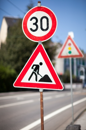 symbolization: Traffic sign for roadworks ahead at the side of an urban road imposing a reduced speed limit