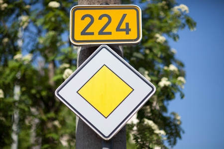 symbolization: Yellow diamond priority or right of way traffic sign under a route marker against tree foliage
