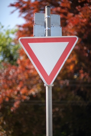 Triangular to yield to traffic on a metal pole against foliage photo