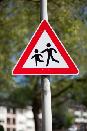 symbolization: Traffic warning sign for children playing mounted on a pole in an urban environment against greenery telling motorists to slow down and be aware