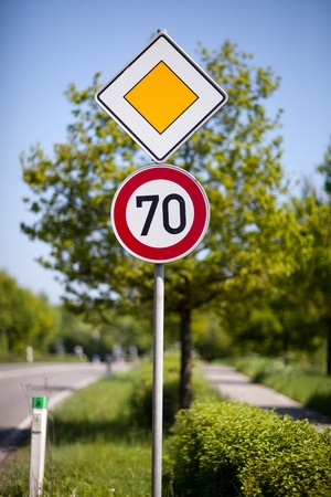 symbolization: Speed limit road sign of 70 kilometres per hour on the side of a rural road Stock Photo