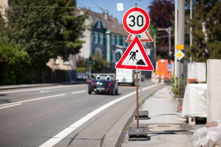 Temporary reduce speed limit for roadworks ahead sign standing on the roadside of an urban street with traffic and shallow dof