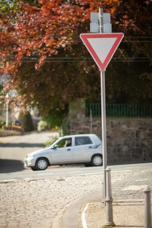 symbolization: Yield sign to control the flow of traffic at an intersection with a passing car Stock Photo