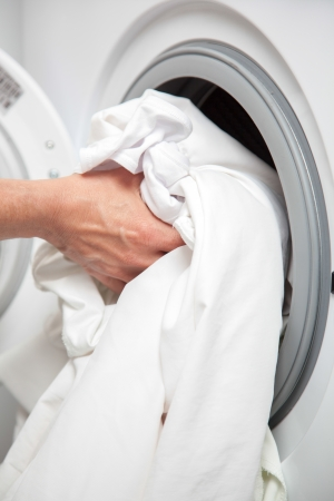 A house woman is filling the the washing machine with some dirty clothes