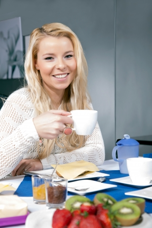 Pretty woman enjoying her breakfast seated at a table with a cup of hot coffee in her hands and a roll with cheese on her plate photo