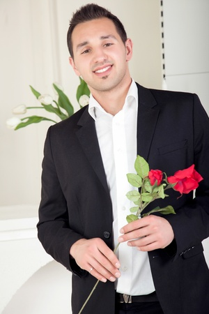 assignation: Smiling romantic young man about to propose to his girlfriend nervously holding a long stemmed red rose in his hands
