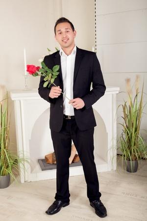 suitor: Corteggiatore romantico portando una rossa a gambo lungo rosa attende nervosamente per la sua ragazza nel suo abito da sera