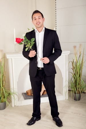 assignation: Romantic suitor carrying a long stemmed red rose waits nervously for his girlfriend in his evening attire