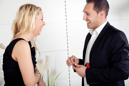 accepts: Overjoyed couple smiling at each other with love as she accepts his offer of marriage and the engagement ring