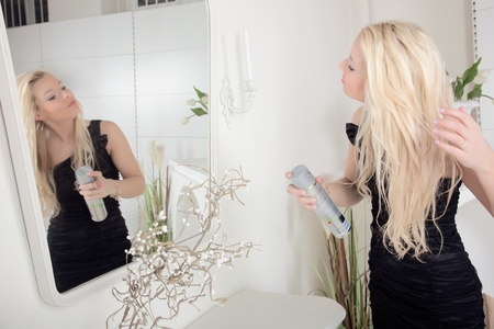 Woman applying hairspray to her long blond hair while looking at herself in a large mirror as she dresses for a date