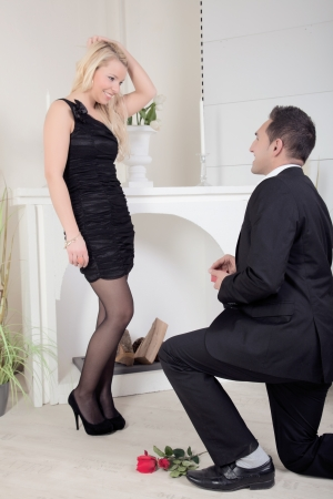 Man proposing kneeling on the floor in front of a beautiful blond woman with a ring box in his hand and red rose lying on the floor photo
