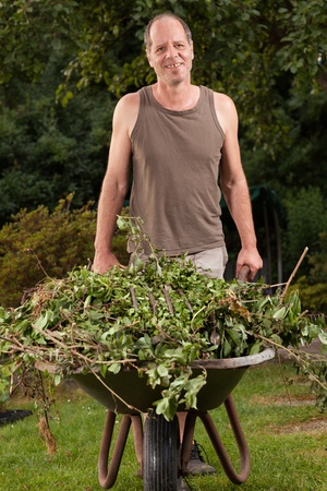 A Gardener is carrying some garden waste with a hand barrow  photo