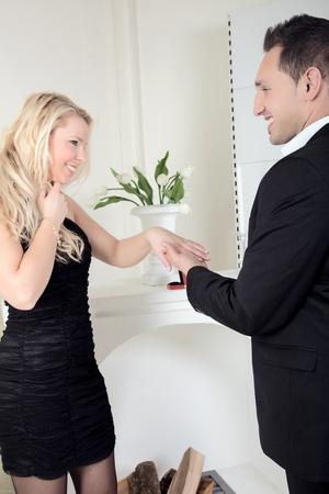 suitor: Felice coppia appena impegnata in piedi sorridente in eacg occhi degli altri come l'uomo tiene la mano fidanzate ammirando il nuovo anello Archivio Fotografico