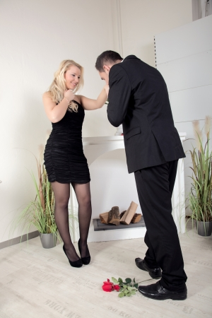 Chivalrous young man proposing to a beautiful woman stooping to kiss her hand with a longstemmed red rose lying at his feet