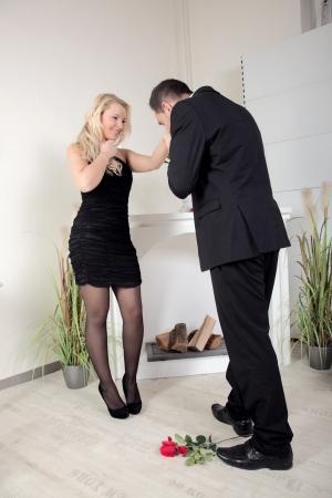 Ridderlijke jonge man voorstelt om een mooie vrouw bukken om haar hand te kussen met een longstemmed rode roos aan zijn voeten liggen Stockfoto