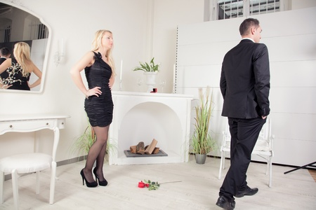 jilted: A couple having some trouble in front of a fireplace with a single red rose lying on the floor between them marking a special occasion  Stock Photo
