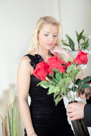 assignation: Man presenting a woman with a bunch of red roses in vase as a gift that appear to leave her completely unmoved Stock Photo