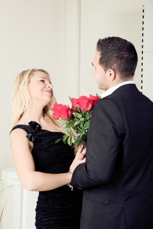assignation: Loving young couple smiling at each other over a large bouquet of red roses as they stand looking into each others eyes Stock Photo
