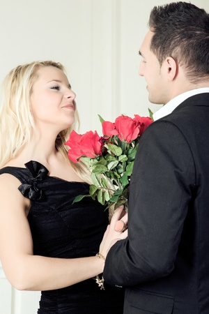 assignation: Romantic loving couple smiling at each other over a large bunch of red roses as they celebrate a special occasion on a night out together Stock Photo