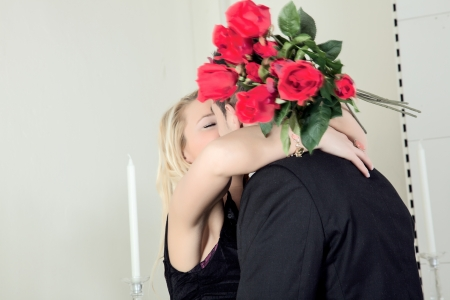 assignation: Happiness is love as an amorous woman hugs and kisses her beau or suitor while holding a large bunch of red roses in her hand behind his neck Stock Photo